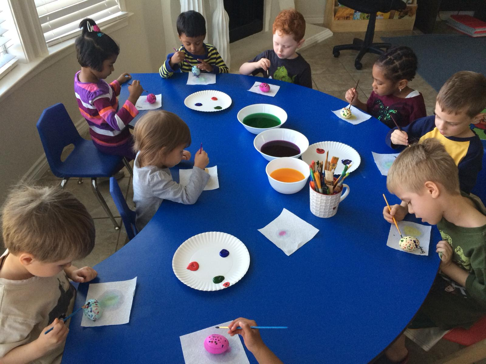 Kids sitting at a table and painting